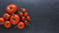Different organic tomato varieties on a dark stone kitchen table