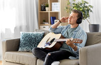 man in headphones playing guitar at home