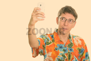 Studio shot of man taking selfie picture with mobile phone