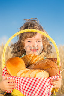 Happy child with bread in basket