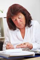 Seniorin mit Euromünzen auf Hand