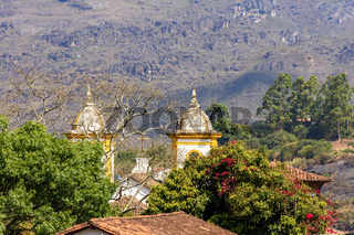 Historic church tower in baroque and colonial style from the 18th century amid the hills and vegetation
