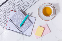 Flat lay home business desk with communication device with cup of tea and writing tools.