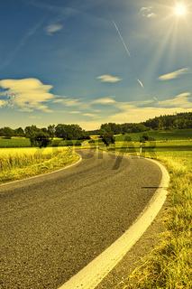 Eine kurvige Landstraße führt durch eine Landschaft