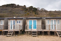 Wooden summer holiday Chalets stand on stilts on the edge of Monmouth Beach, Lyme Regis, England