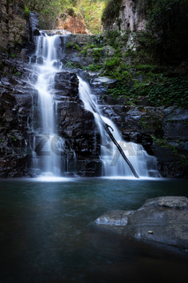 Waterfall tumbling over a ledge into a beautiful swimming hole below