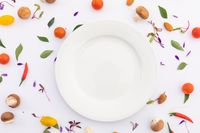 White plate surrounded by fresh vegetables on white background