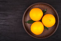 three oranges with green leaves lie in a brown plate on a brown table