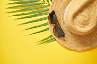 Straw hat, green palm leaf and sunglasses on yellow backdrop. Summer concept. Flat lay, top view