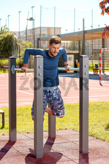 Young man training outside in the park at parallel bars