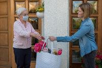 Seniorin mit Mundschutz erhält Einkäufe von Nachbarin