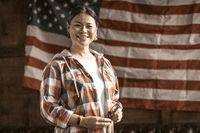 Smiling Asian Woman Proudly Posing On Striped America's Flag Back