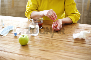 Mature woman with pills and cup of tea