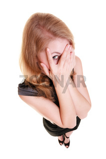 Shy afraid woman peeking through fingers isolated.
