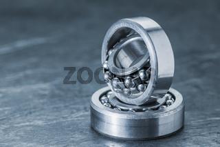 Two spherical roller bearings on slate blue toned
