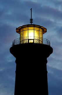 beleuchtete Leuchtturmspitze in der Dämmerung vor einem tiefblauen Abendhimmel