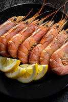 Boiled tiger prawns on black plate. Tasty shrimps.