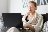 Stay at home and social distancing. Woman in her casual home bathrobe working remotly from her living room. Video chatting using social media with friend, family, business clients or partners