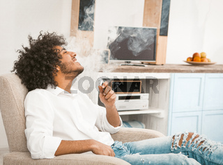 Hipster smoker smoks electronic cigarette at home. Overgrown shaggy handsome man did not cut his hair in quarantine for a long time. Tinted image