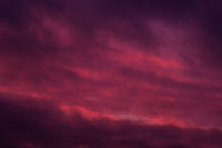 Full frame view heavy moody sky cloudscape bright pink violet colors