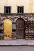 Blocked arced door, wooden door, and small windows with rusted bars on black and red bricks wall