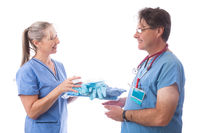 Hospital healthcare worker hands a PPE kit to another nurse or doctor