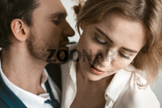 Sexy couple of business people in love. Close up portrait. Man going to kiss female neck. Selective focus on happy smiling female face in foreground