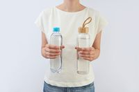 Glass and plastic bottles of clean fresh water in a woman's hands.