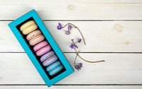 Macaroons in gift box next to violet