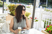 Woman drinking latte coffee and eating ice cream in outdoor cafe