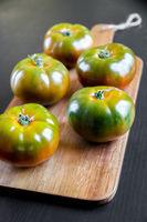 Black Krim organic tomatoes on a cutting board