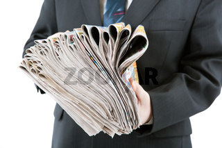 man's hands holding a stack of newspapers