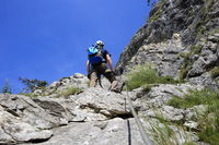 Mann klettert am Klettersteig in den Alpen