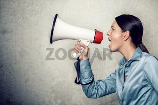 Frau ruft laut mit einem Megafon