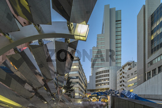 Futuristic architecture with mirroring panels swiveling in Shibuya district in Dogenzaka street lead