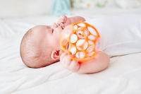 Baby hält Rassel Ball in Hand