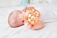 Baby hält Rassel Ball in Hand