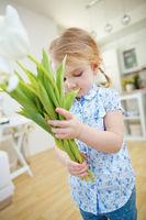 Mädchen trägt Blumenstrauß mit weißen Tulpen
