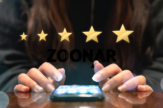 Woman filling out 5 star gold customer service feedback survey on electronic mobile device after online shopping experience - Business satisfaction ratings, retention and quality of service concepts