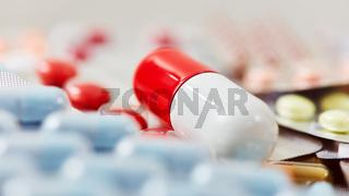 Große Pille liegt auf bunten Medikamenten