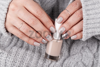 Manicured woman hands holding nail polish