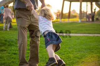 Vater dreht Tochter im Kreis