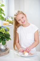 Kind beim Schälen von Ei in Küche