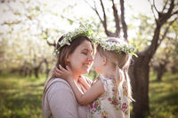 Happy mother and her little daughter in the spring day in a blossoming garden