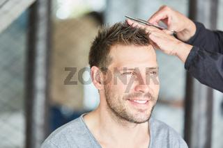 Mann bekommt einen Haarschnitt  beim Friseur