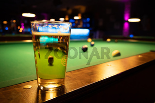 in a billiard parlor on the rail of a pool table is a glass with a beer