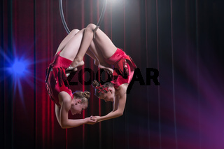 Circus actress acrobat performance. Two girls perform acrobatic elements in the air ring.