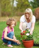 Mutter und Kind bei Gartenarbeit im Sommer