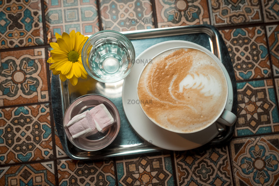cappuccino in a white cup on a white saucer with two pieces of marshmallow