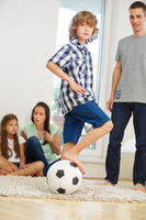 Familie mit Fußball im Wohnzimmer